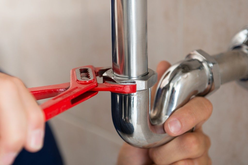 plumber fixing pipe with wrench
