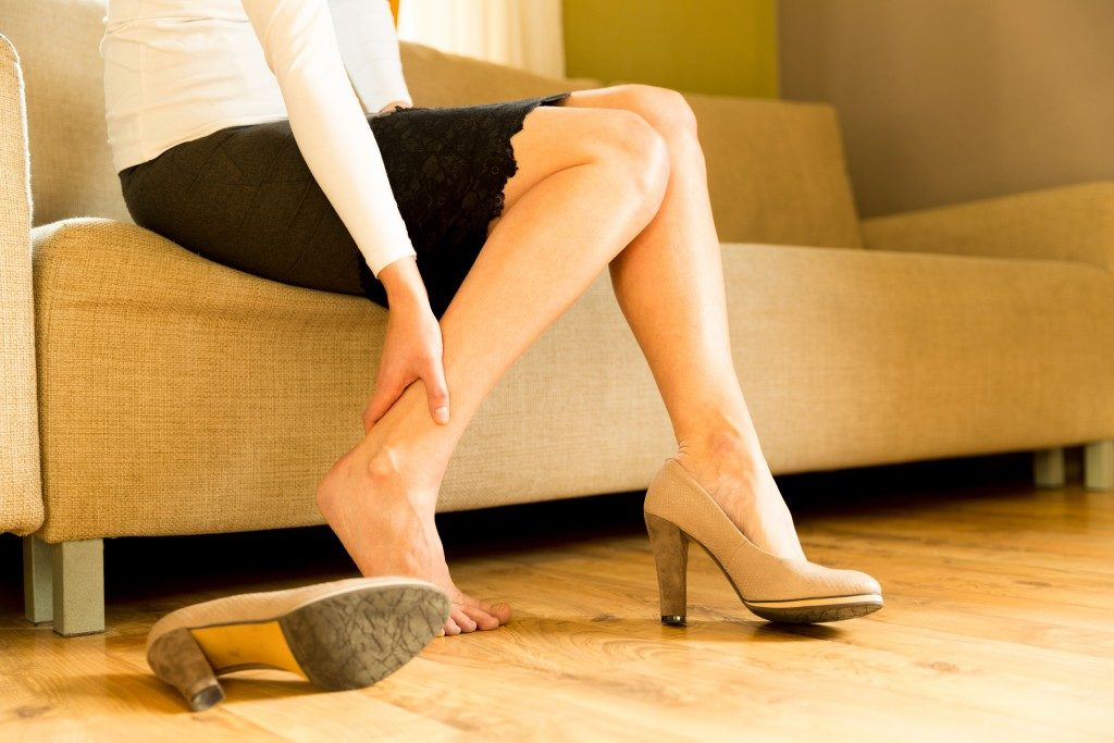 Female removing heels while sitting on couch