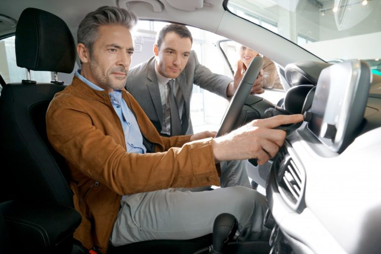 Man checking the specs of a car with car salesman