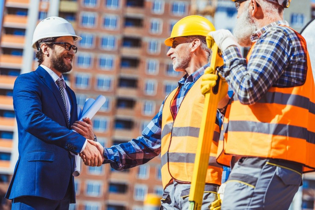engineers shaking hands with businessman