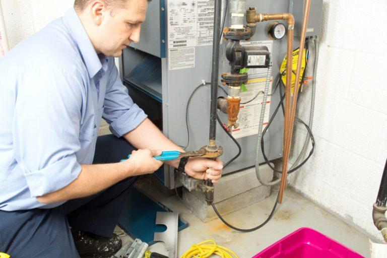 man fixing a furnace