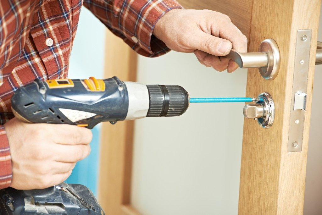 man drilling the lock on the door