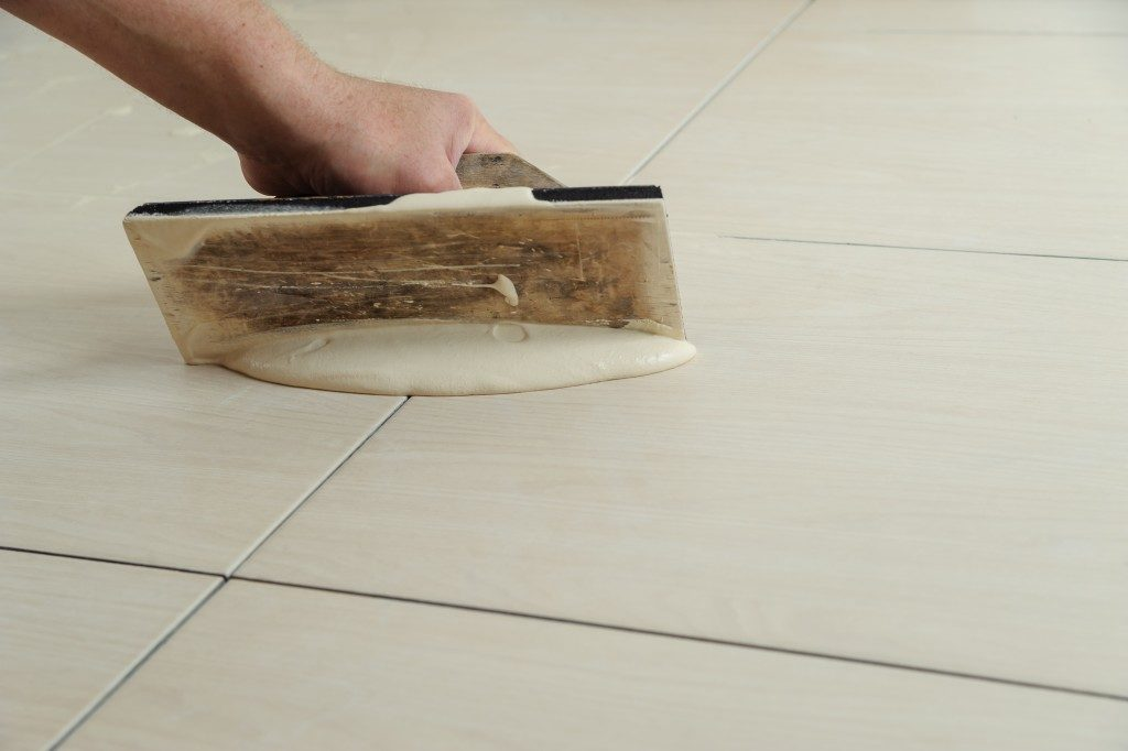 person applying grout on the floor