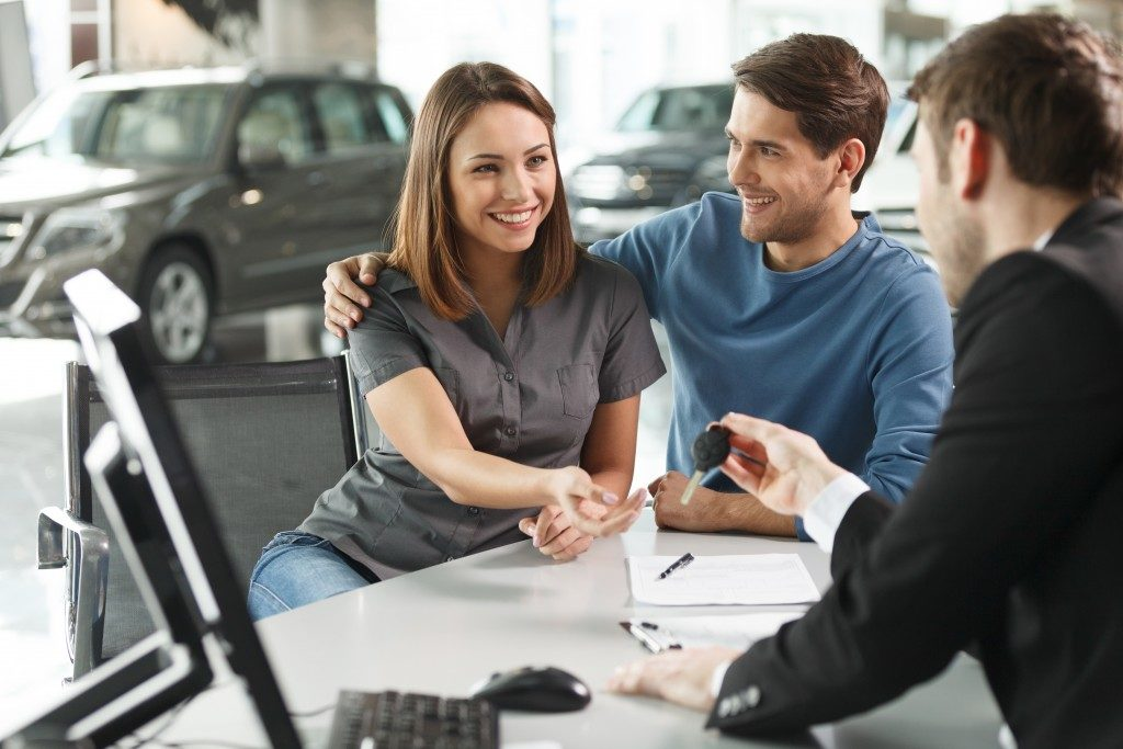 Couple receiving keys of bought car