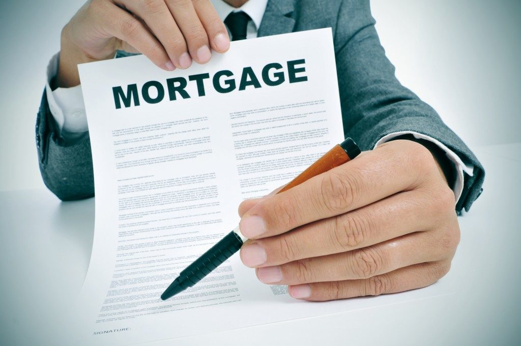 man holding a mortgage contract and a pen