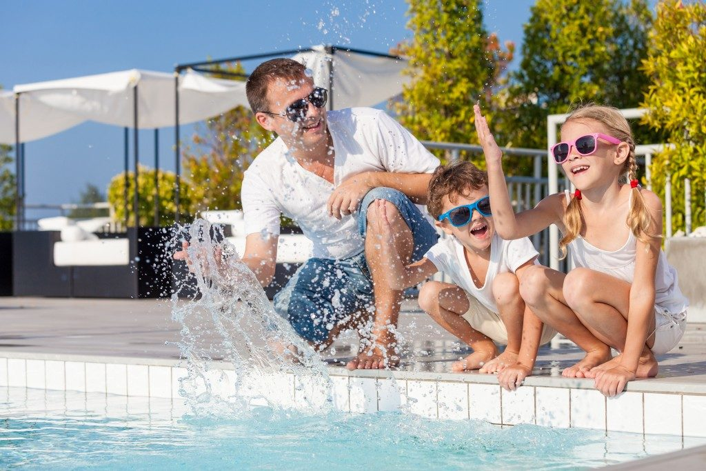 father with kids having fun in the pool